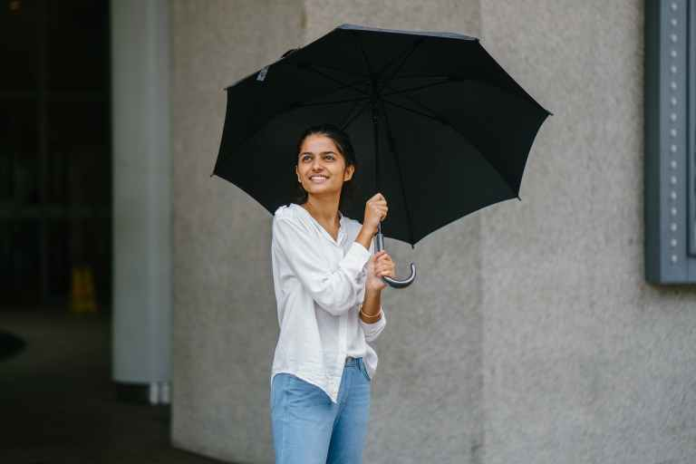 woman in white button up long sleeved shirt holding black umbrella
